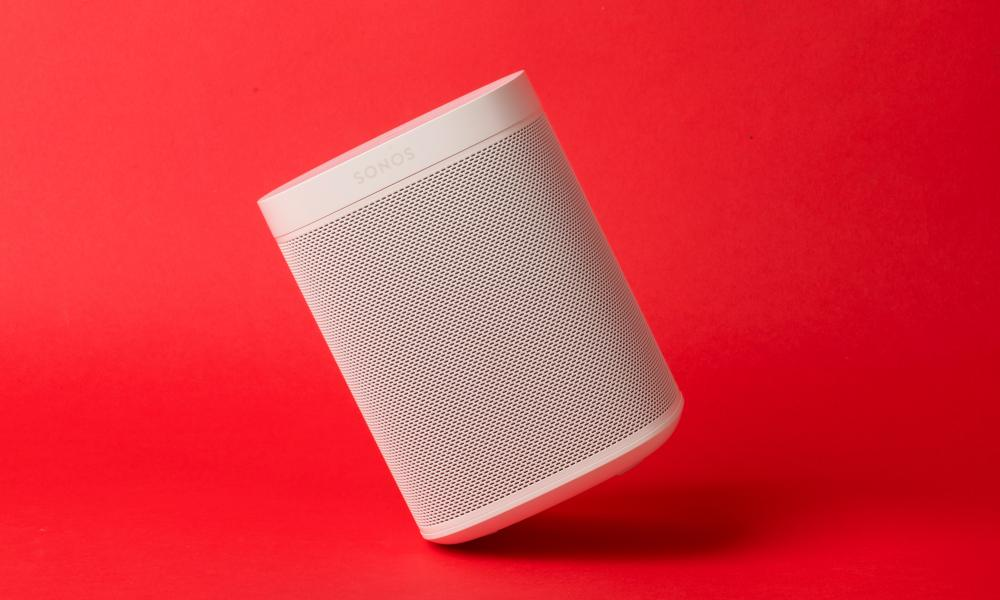 the sonos one speaker tilted at an angle against a red background