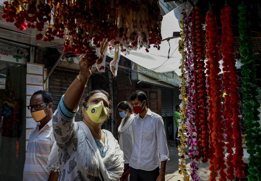 A woman looks for decorations at a roadside stall ahead of Diwali, in Kolkata, India. India's confirmed coronavirus caseload surpassed 8 million on Thursday with daily infections dipping to the lowest level this week, as concerns grew over a major Hindu festival season and winter setting in.