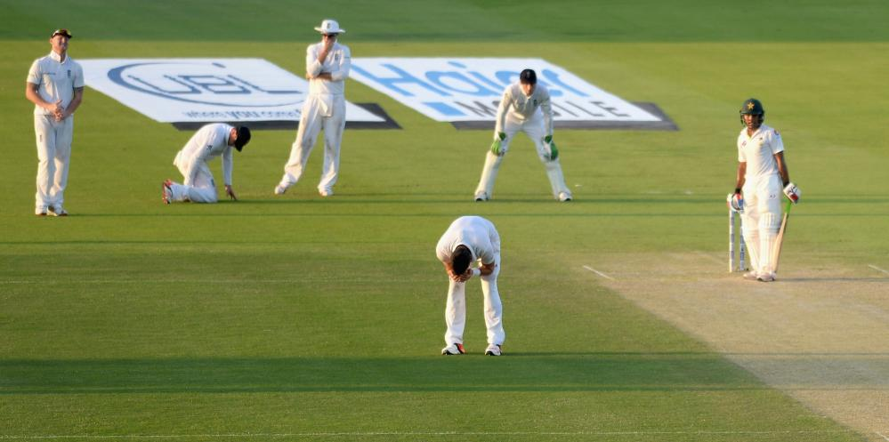 James Anderson of England reacts after Ian Bell, second left, drops Shoaib Malik.