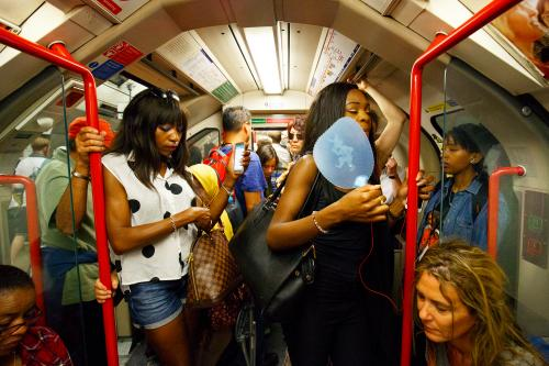 A woman uses a fan to stay cool on the tube in London, where delight at the arrival of summer sunshine is offset by sweltering conditions on public transport