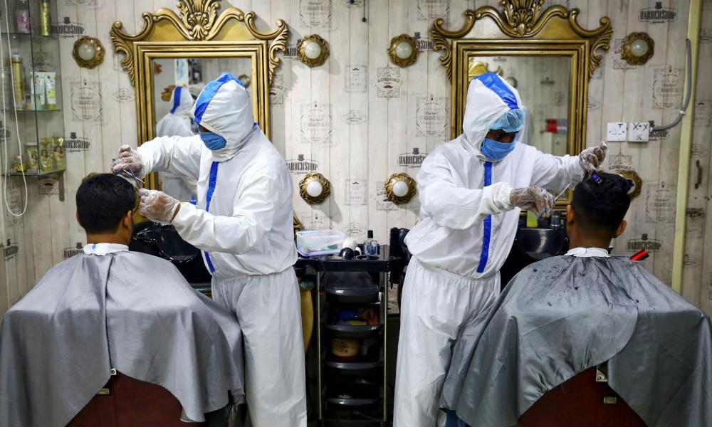 Barbers wearing protective suits and face masks cut hair at a salon in Dhaka, Bangladesh.