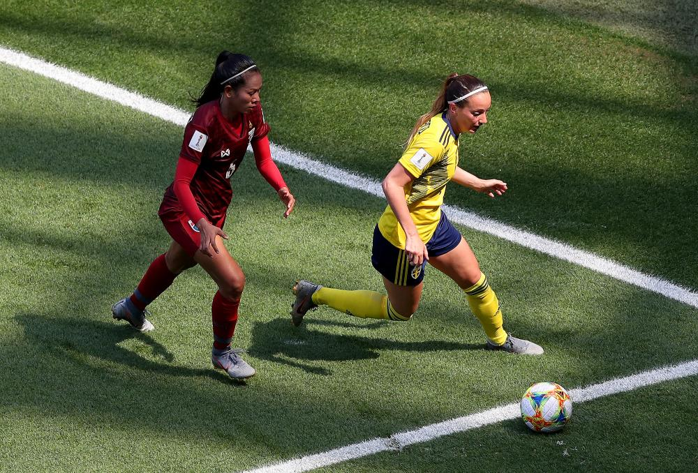 Kosovare Asllani of Sweden under pressure from Pikul Khueanpet of Thailand.