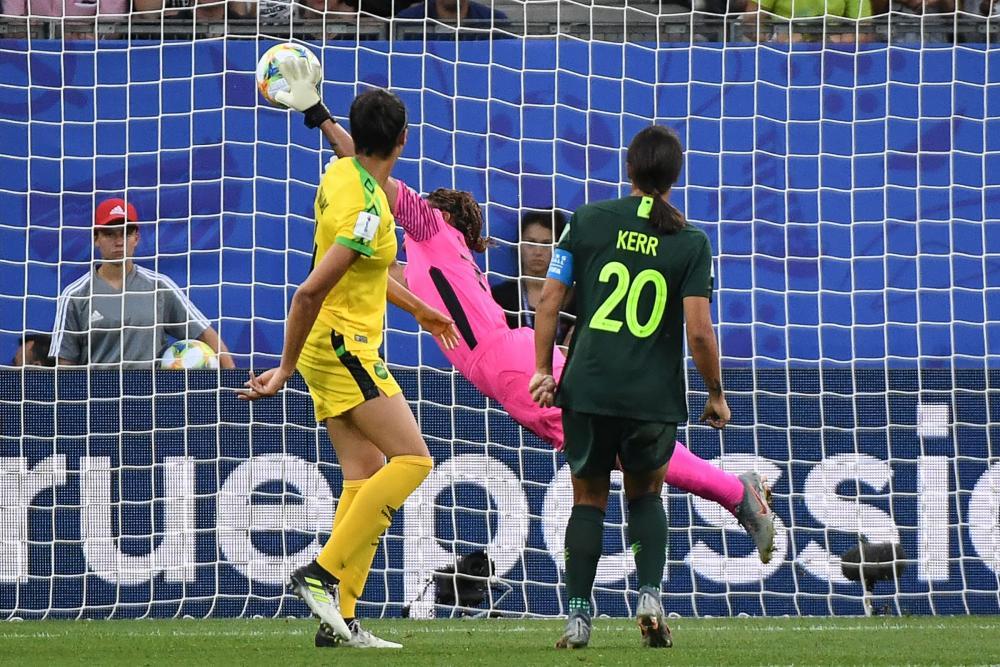 Samantha Kerr heads in the opening goal past Jamaica's goalkeeper Nicole McClure.