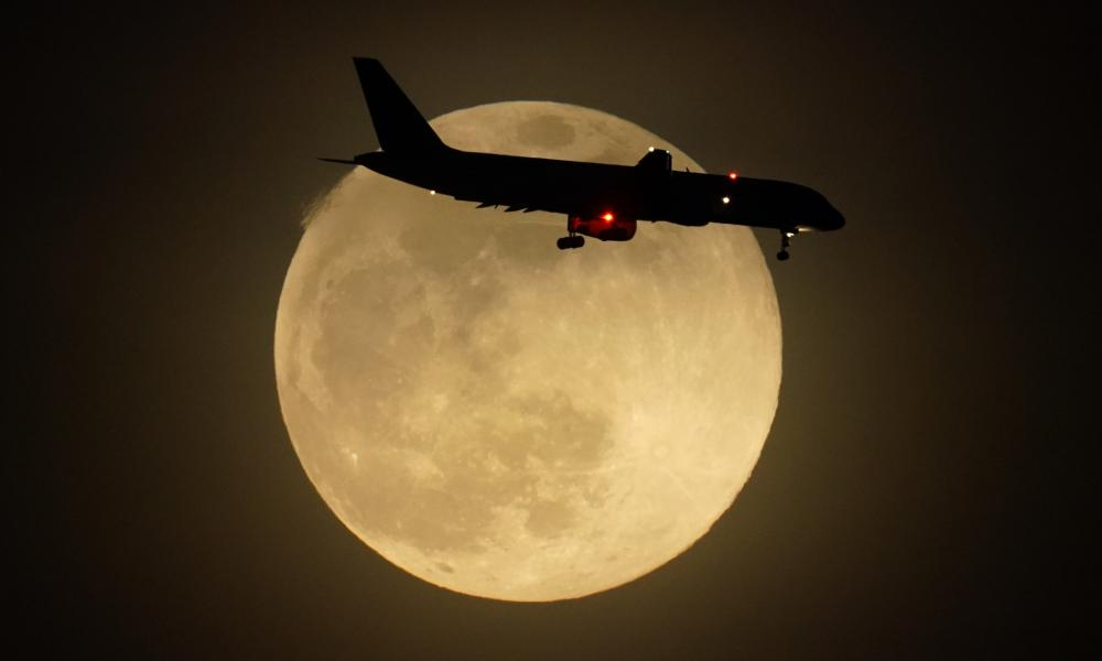 A jet is silhouetted by the rising moon as it approaches Louisville international airport in Kentucky on Monday.