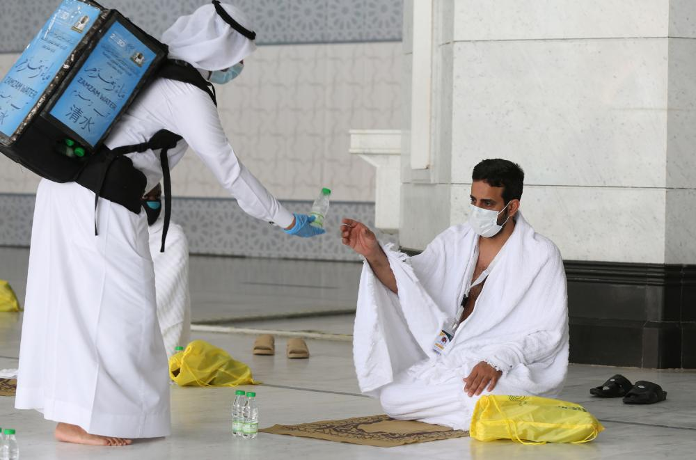 A pilgrim receiving bottled water at the Grand Mosque complex in the holy city of Mecca, at the start of the annual hajj pilgrimage.