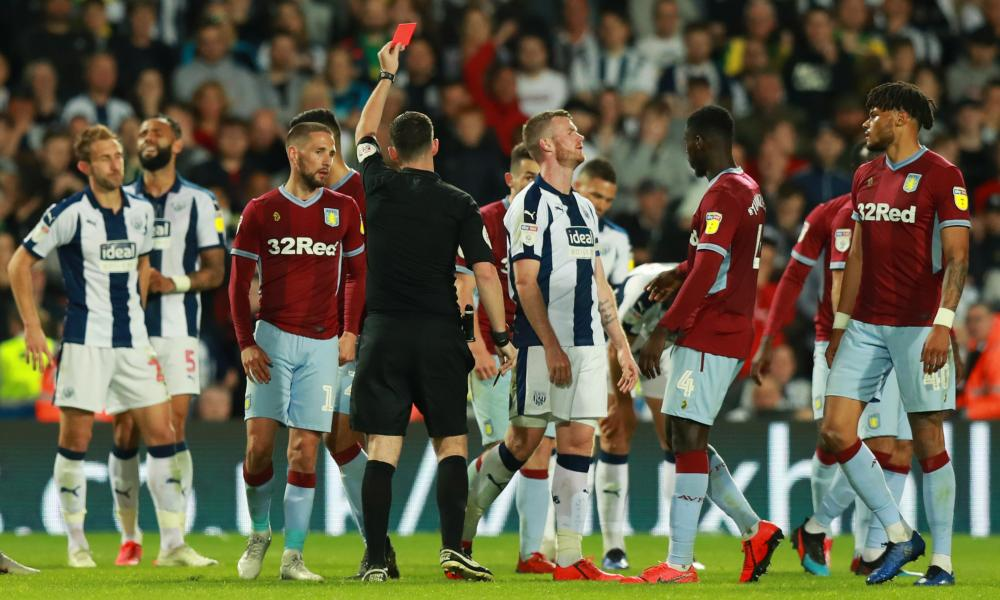 Chris Brunt of West Bromwich Albion (centre) reacts as he is shown a red card by referee Chris Kavanagh and is sent off.