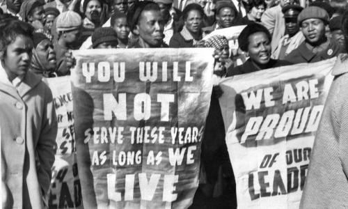 African women demonstrate in front of the Law Courts in Pretoria, 16 June 1964, after the verdict of the Rivonia trial, in which eight men, among them anti-apartheid leader and member of the African National Congress (ANC) Nelson Mandela, were sentenced to life imprisonment. The eight men were accused of conspiracy, sabotage and treason. (Photo credit should read OFF/AFP/Getty Images) HORIZONTAL|JUSTICE|TRIAL|DEMONSTRATION|HUMAN RIGHTS|APARTHEID|ANC|WOMAN|PLACARD|CROWD|BLACK POPULATION|BLACK POPULATION