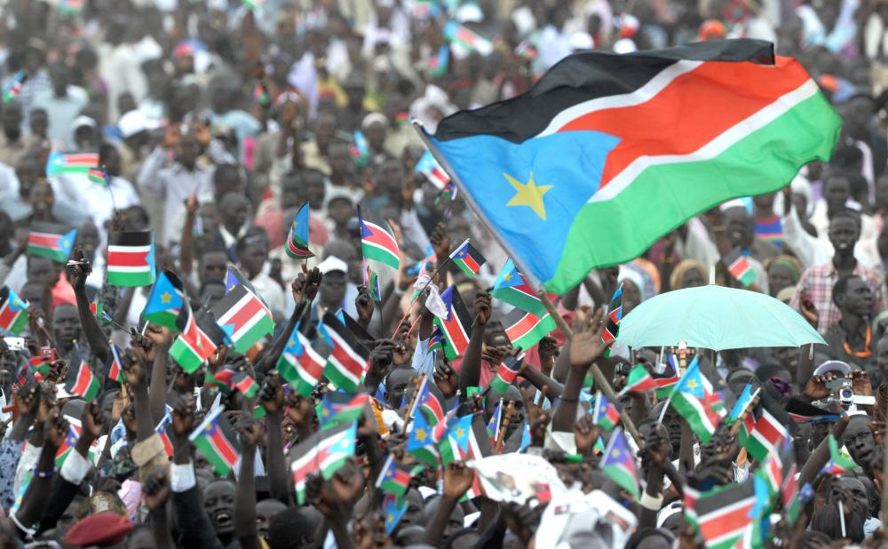 Thousands of Southern Sudanese wave the flag of their new country, 9 July 2011