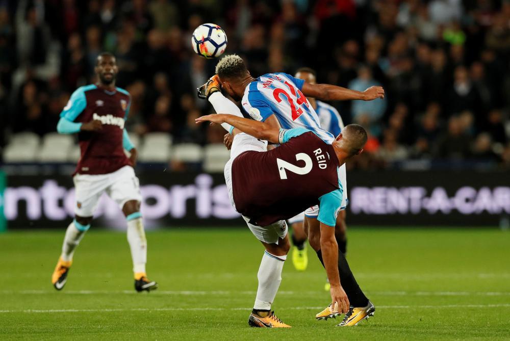 Winston Reid kicks Huddersfield Town's Steve Mounie in the face.