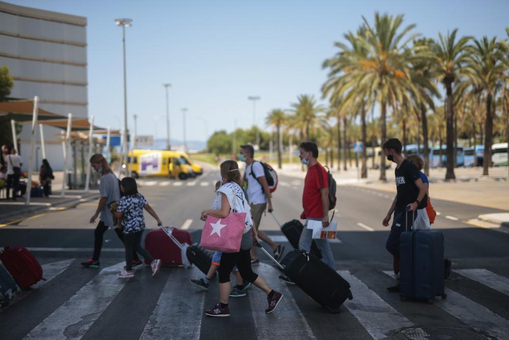 Passengers arrive at Son Sant Joan airport on the Spanish Balearic island of Palma de Mallorca on Sunday.