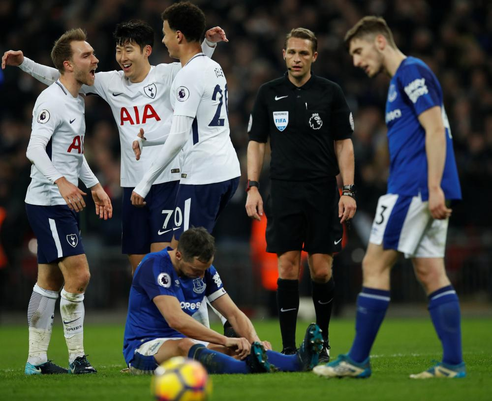 Tottenham's Christian Eriksen celebrates scoring their fourth goal with team mates while Everton's Phil Jagielka looks dejected.