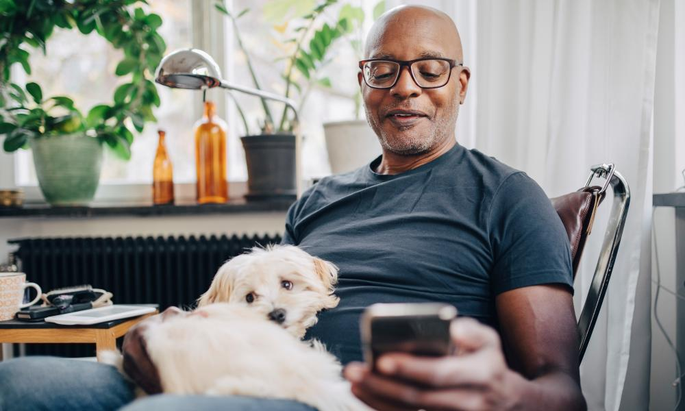 Smiling retired senior male using smart phone while sitting with dog in room at home