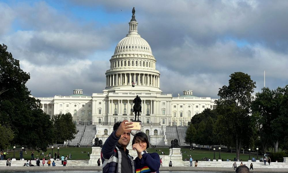 A couple taking a selfie front of the US Capitol Building.