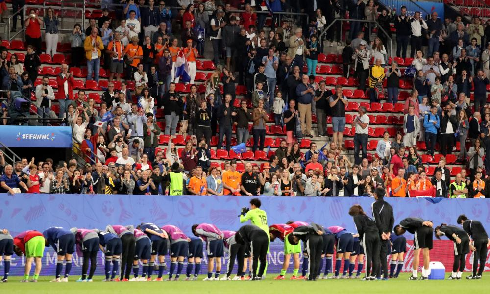 The Japanese players and coaching staff are applauded by fans as they bow to their supporters after their defeat.