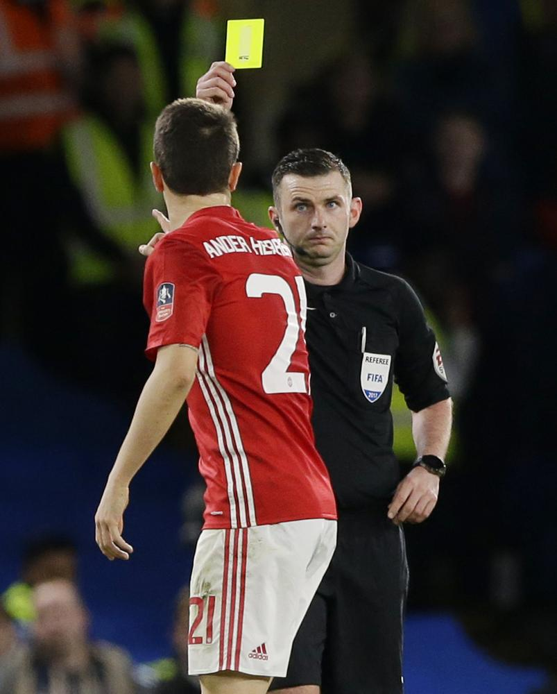 Referee Michael Oliver shows the yellow card to Ander Herrera
