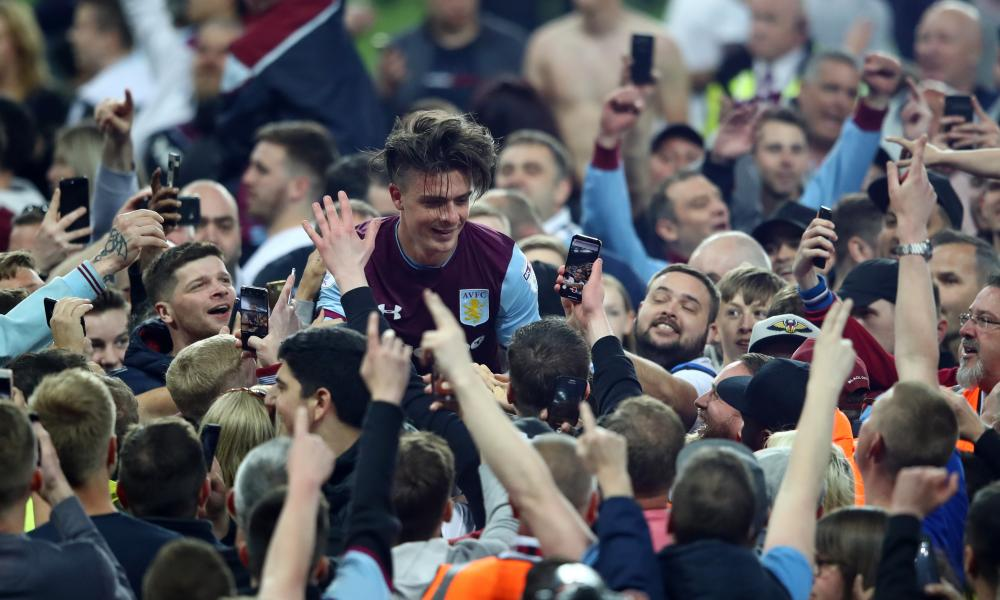 Jack Grealish of Aston Villa is seen at the full time whistle as fans invade the pitch.