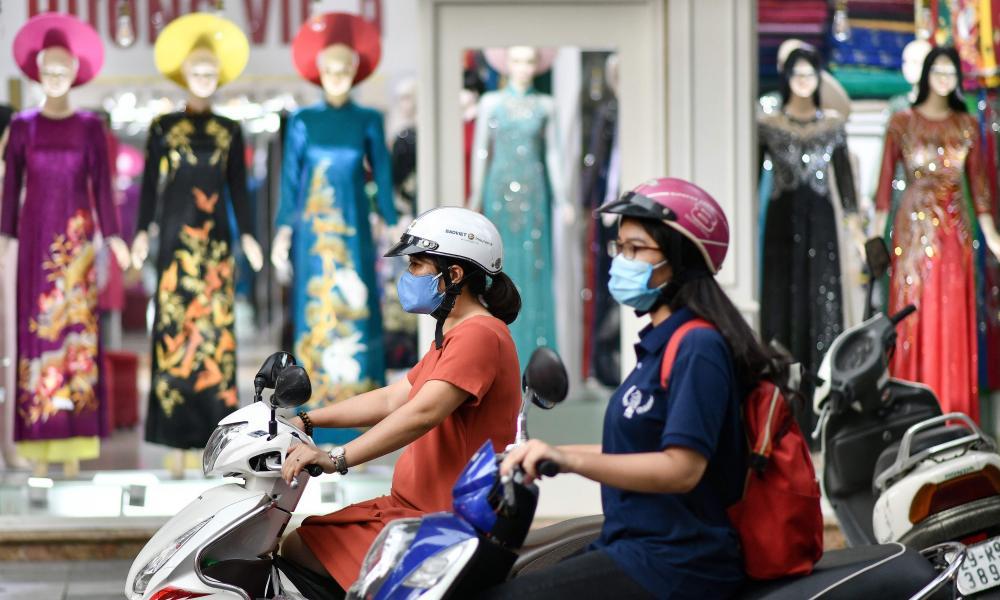 Women wearing face masks ride past a shop in Hanoi, Vietnam.