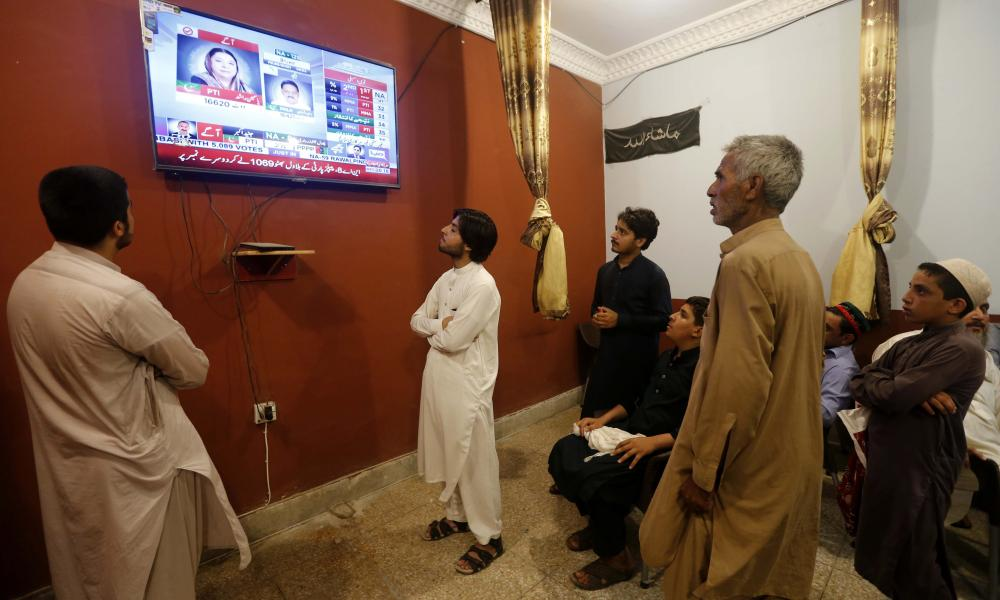 People watch reports on preliminary and unofficial results of general elections, in Peshawar, Pakistan