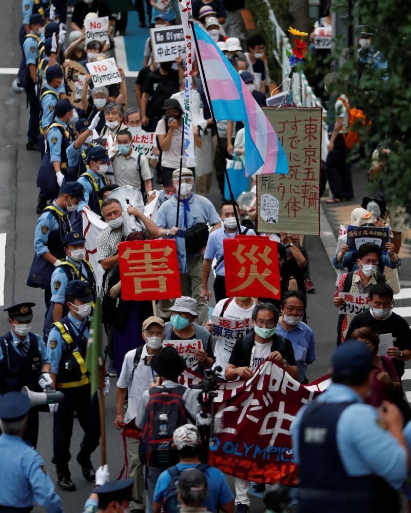 Demonstrators wearing face masks hold signs to protest against the Tokyo 2020 Olympic Games a year before the start of the summer games that have been postponed to 2021 due to the coronavirus outbreak, near National Stadium in Tokyo, Japan on Friday.