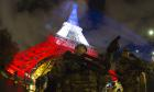 A French soldier enforcing the Vigipirate plan, France's national security alert system, is pictured on November 17, 2015 in Paris in front of the Eiffel Tower, which is illuminated with the colors of the French national flag in tribute to the victims of the November 13 Paris terror attacks. AFP PHOTO / JOEL SAGETJOEL SAGET/AFP/Getty Images