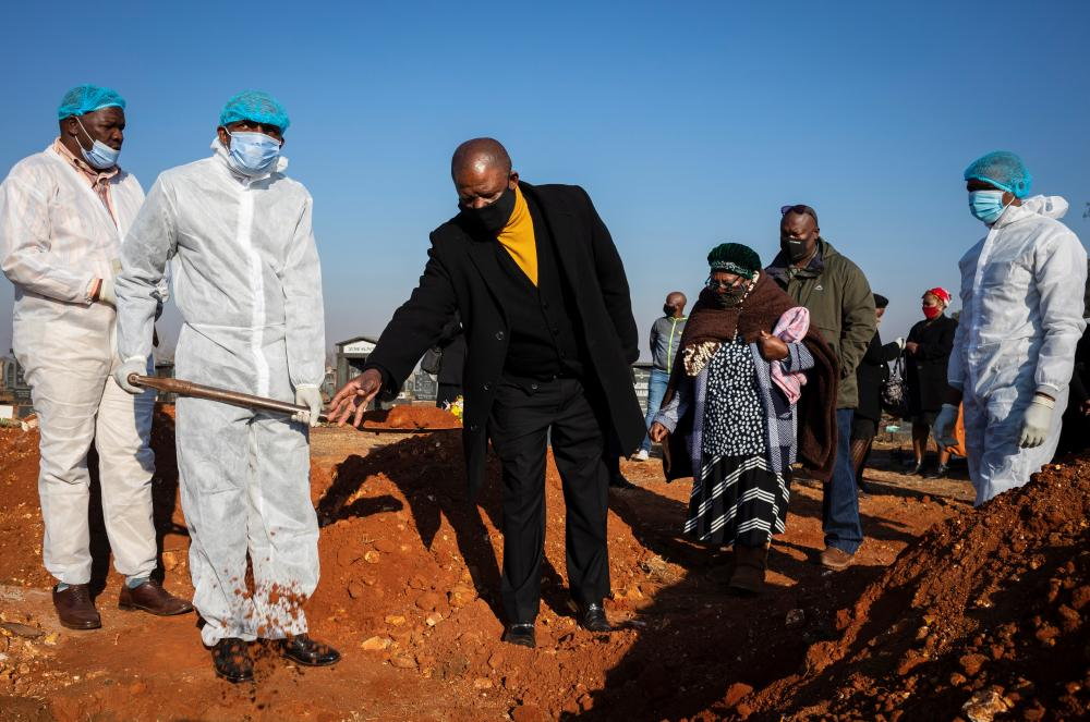 Mourners stand at the gravesite of a family member who died as a result of Covid-19 in Johannesburg, South Africa, on 24 July 2020.