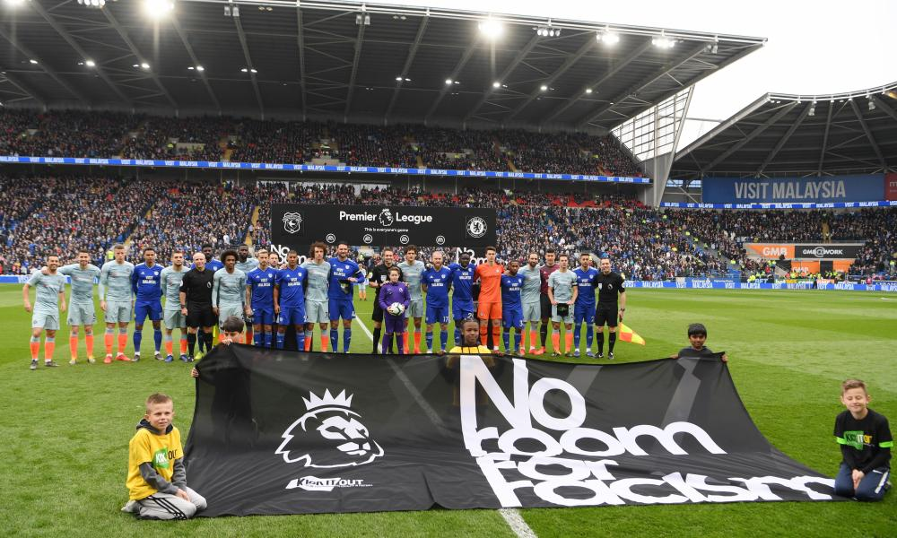 Both teams line up in front of the No room for racism sign.