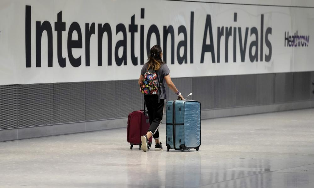 A passenger arrives from a flight at Terminal 5 of Heathrow Airport in London.