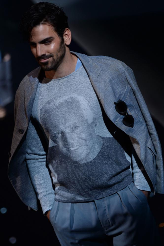 A model presents a T-shirt featuring a vintage image of Georgio Armani.