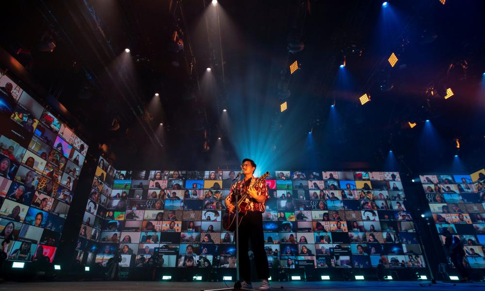 An artist performs as screens show audience via the Zoom application during the first six-hour online music festival at a studio amid the spread of the coronavirus disease (COVID-19) in Bangkok, Thailand, June 7, 2020. REUTERS/Athit Perawongmetha