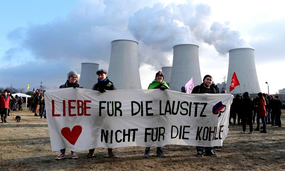 "Climate activists from Fridays for Future and Ende Gelaende protest at the Jänschwalde power station in Lusatia in 2019. The banner reads: ""Love for the Lausitz. Not for the coal."""