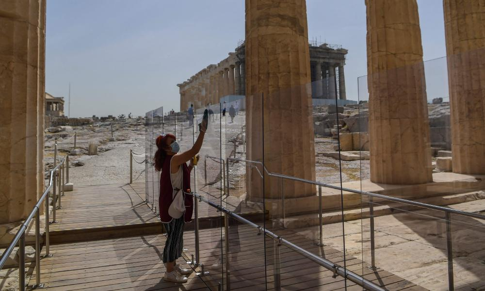 A worker cleans a plexiglass divider at the entrance of the Acropolis in Athens.