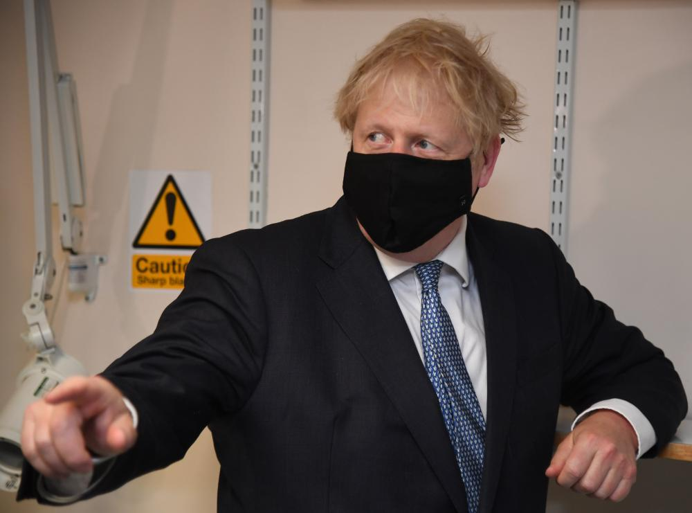 Boris Johnson wears a face mask as he visits Tollgate medical centre in Beckton, London.