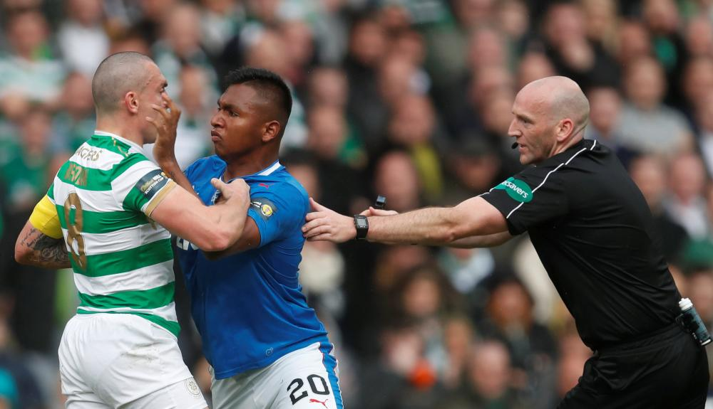 Morelos clashes with Brown as referee Bobby Madden attempts to intervene.