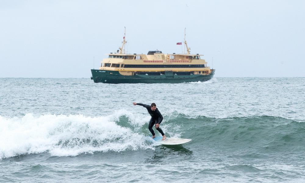 A surfer rides a wave as a Manly ferry passes in the background. Capacity on public transport in New South Wales will be increased from 1 July as coronavirus restrictions ease.