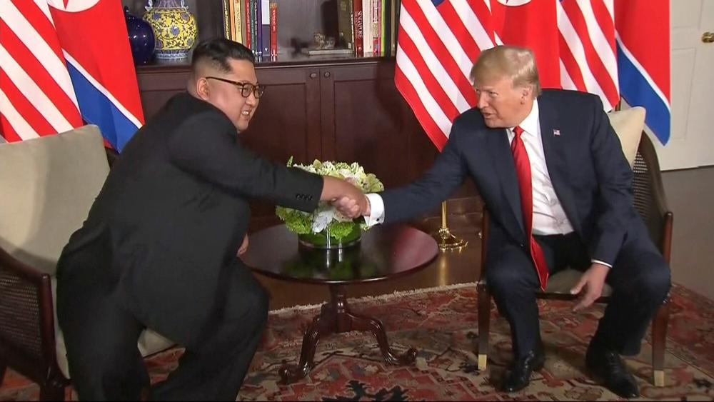 Donald Trump and Kim Jong-un shake hands before their meeting at Capella hotel in Singapore