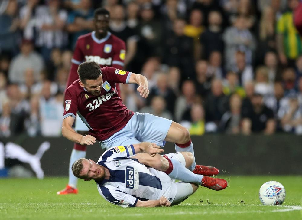 West Bromwich Albion's Chris Brunt is booked after this challenge on Aston Villa's John McGinn.