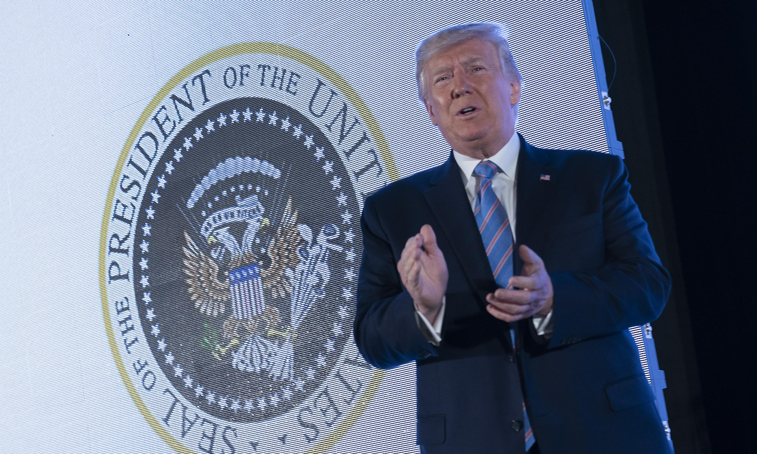 Trump stands before presidential seal doctored with symbols of Russia and golf
