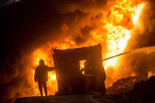 Firefighters work to extinguish an oil well set on fire by fleeing Islamic State group members