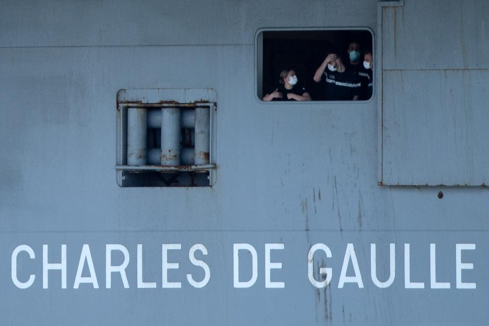 French sailors wearing face masks aboard the aircraft carrier Charles de Gaulle as it arrived in Toulon earlier this week
