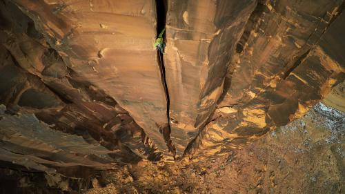 A climber scaling a rock face in Utah