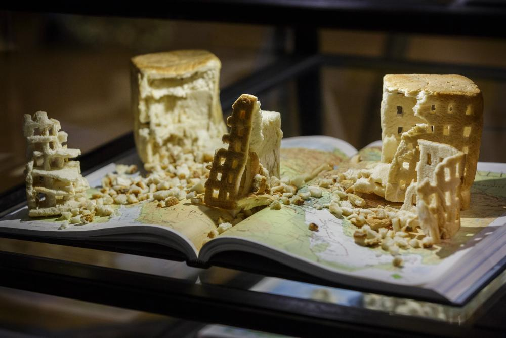 'Even Fiona was quite amazed that these had arrived intact': Crust (2014–15) by Fiona Hall, comprising carved baked bread and atlases.