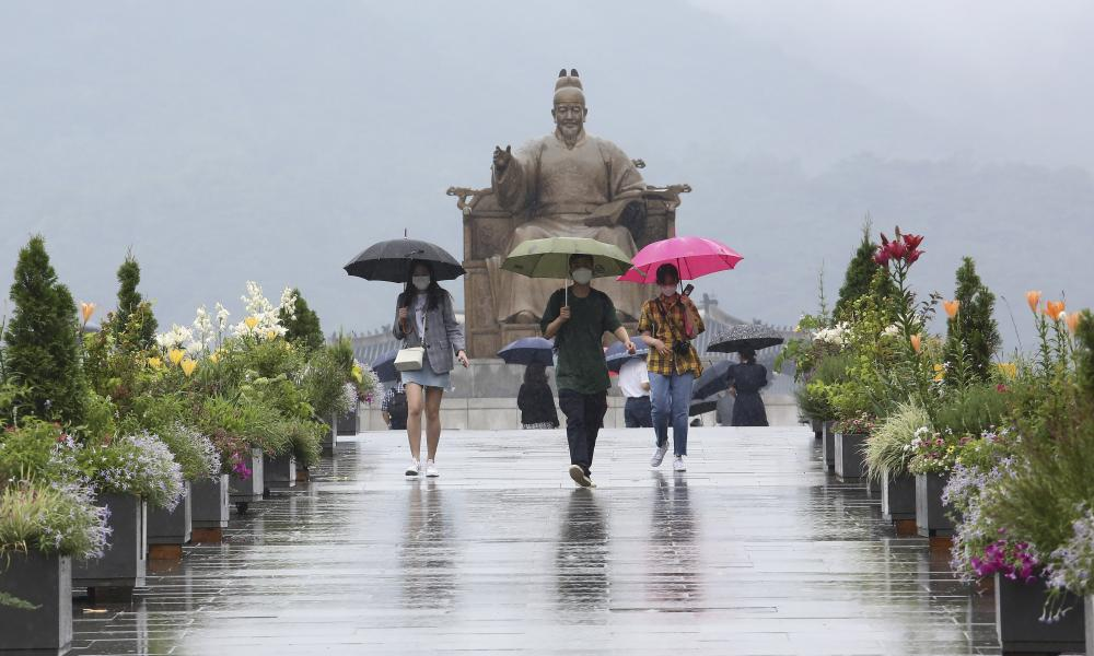 People wearing face masks to help protect against the spread of the new coronavirus pass by the statue of King Sejong in the Joseon Dynasty, at the Gwanghwamun Plaza in Seoul, South Korea, Wednesday, 24 June 2020.