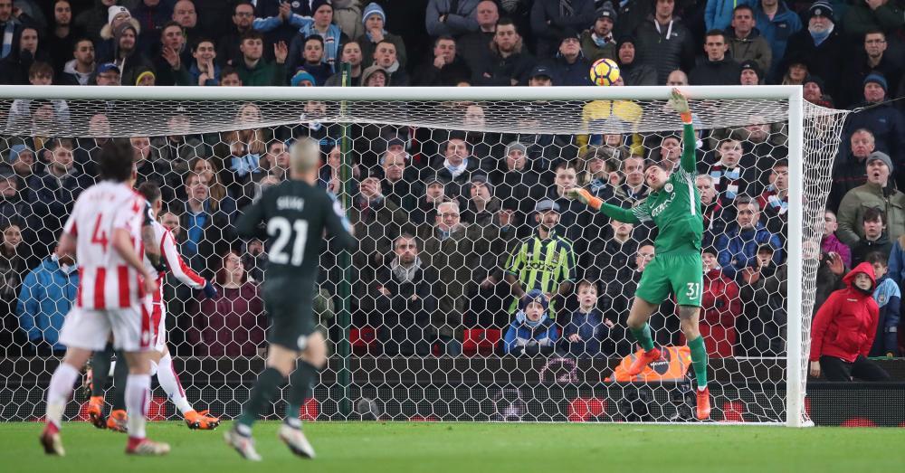 Manchester City goalkeeper Ederson tips the ball over the crossbar.