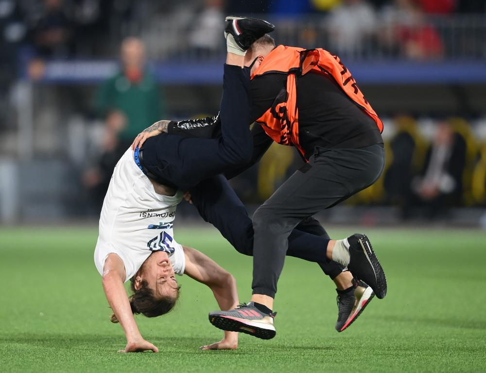 A pitch invader is tackled down by a steward.