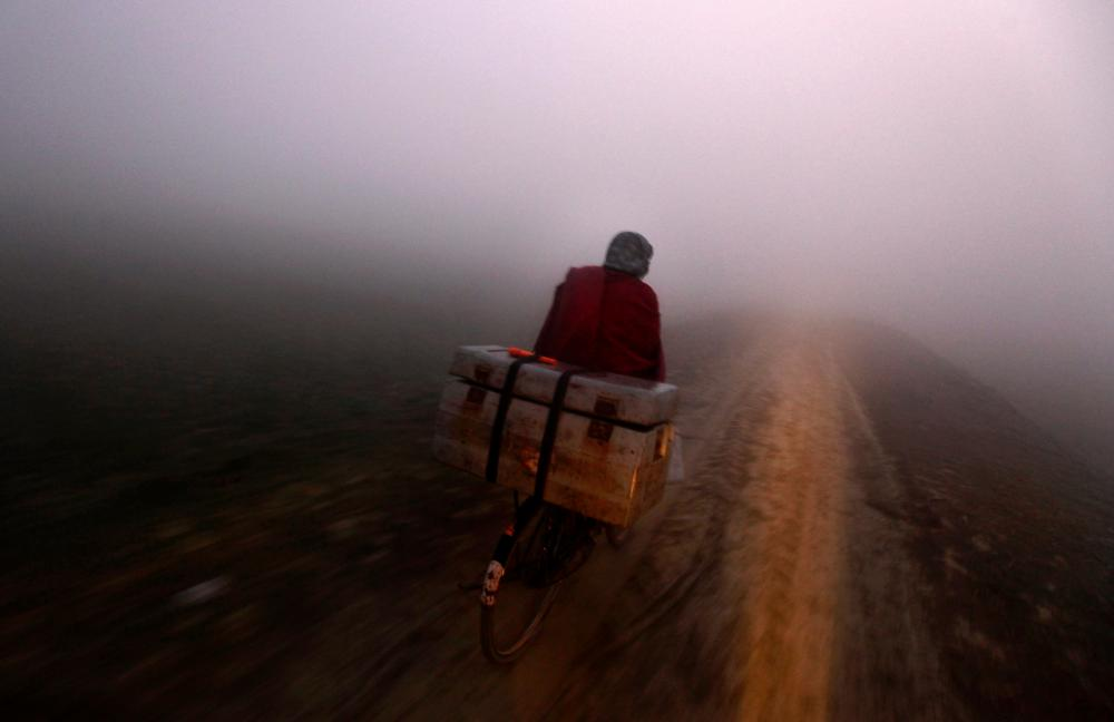 Salit Kumar rides his bike at dawn carrying a box full of polio vaccines to remote villages.