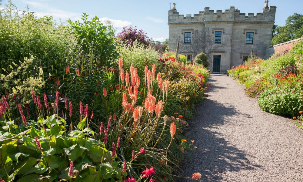 Floors Castle, Kelso, with borders packed with Kniphofia 'Timothy', achilleas, heleniums, crocosmias and alstroemerias.