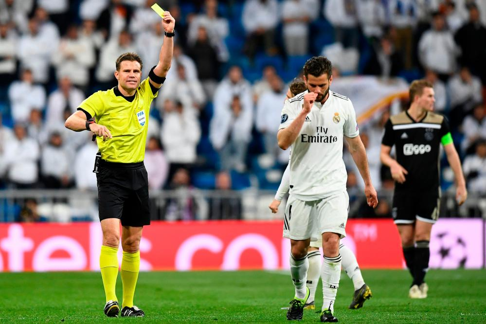 German referee Felix Brych shows a second yellow card to Real Madrid's Nacho Fernandez who walks off the pitch.