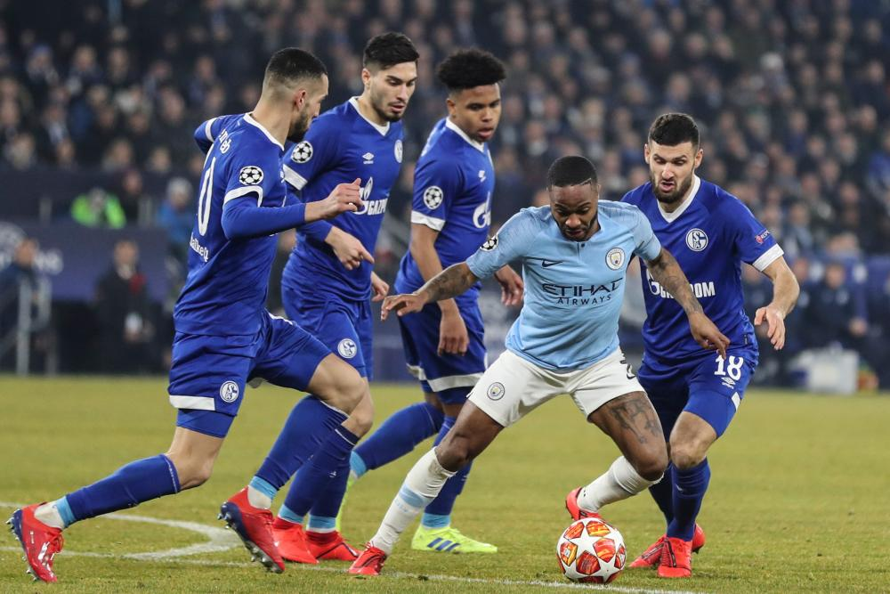 Manchester City's Raheem Sterling is surrounded by Schalke players.