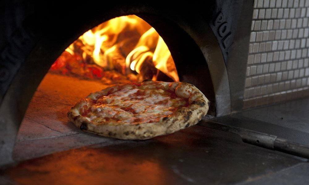Pizza coming out of the oven at Franco Pepe's in Naples, Italy.