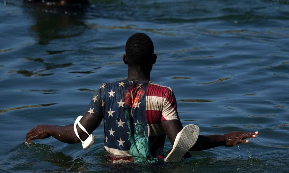 A Haitian migrant wades across the Rio Grande from Del Rio, Texas, to return to Ciudad Acuña, Mexico, to avoid deportation from the US.